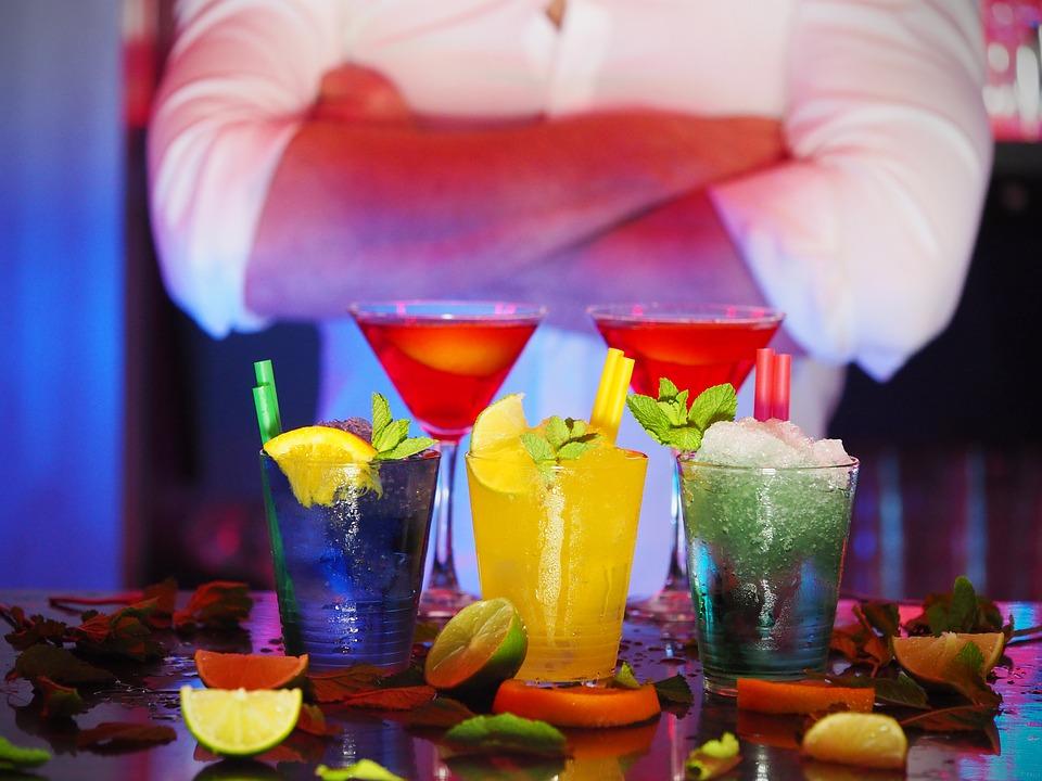 5 cocktails différents préparés et le barman en arrière plan
